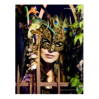 Woman wearing a mask looking out from and iron postcard