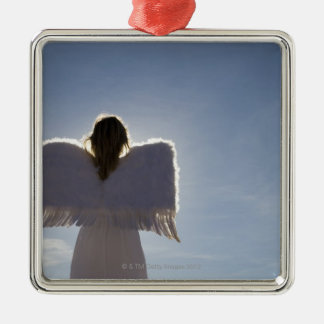 Woman wearing angel wings, rear view, three christmas ornament