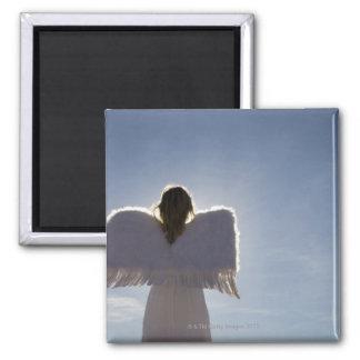 Woman wearing angel wings, rear view, three magnet