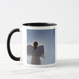 Woman wearing angel wings, rear view, three mug