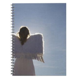 Woman wearing angel wings, rear view, three notebooks