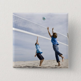 Woman with her grandson playing beach volleyball 15 cm square badge