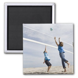 Woman with her grandson playing beach volleyball square magnet