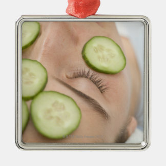 Woman with slices of fresh cucumber on her face, christmas ornament