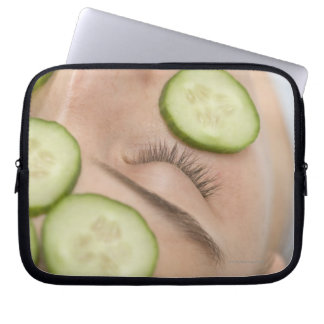 Woman with slices of fresh cucumber on her face, laptop sleeve