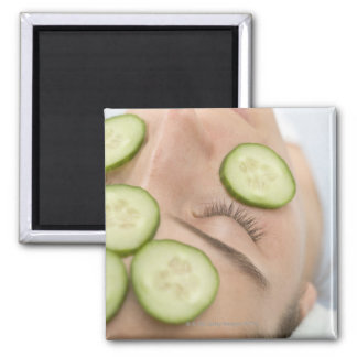 Woman with slices of fresh cucumber on her face, magnet
