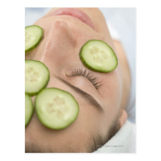 Woman with slices of fresh cucumber on her face, postcard