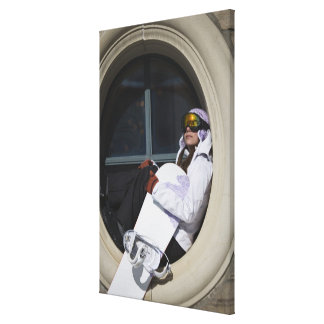 Woman with snowboard sitting in window canvas print