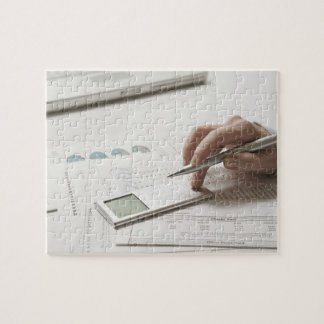 Woman working on financial paperwork and jigsaw puzzle