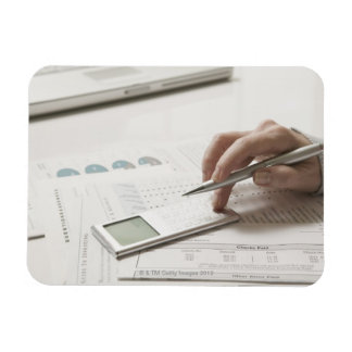 Woman working on financial paperwork and magnet