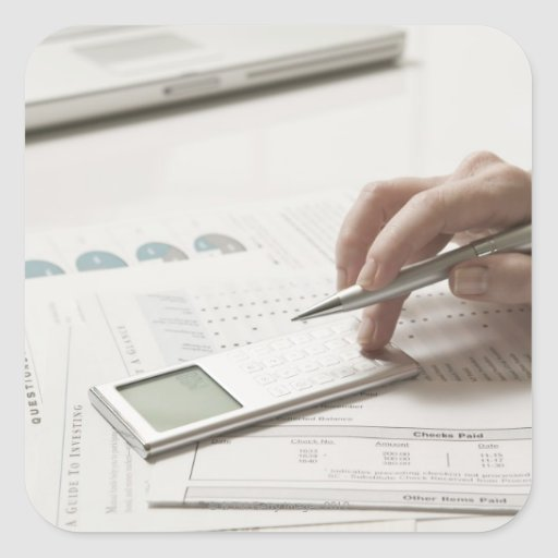 Woman working on financial paperwork and square stickers