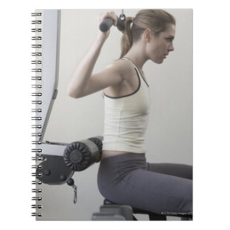 Woman working out with weights notebook