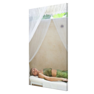 Woman wrapped in banana leaves at a spa in canvas print