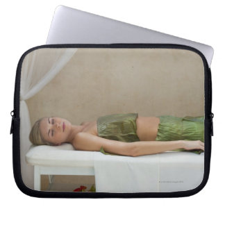 Woman wrapped in banana leaves at a spa in laptop sleeve