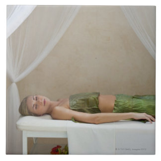 Woman wrapped in banana leaves at a spa in large square tile