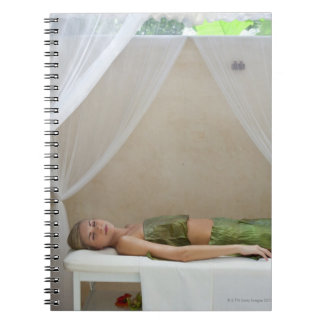 Woman wrapped in banana leaves at a spa in note books