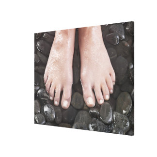 Woman's feet on pebbles canvas print