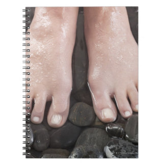 Woman's feet on pebbles notebook