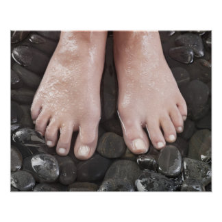 Woman's feet on pebbles poster