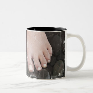 Woman's feet on pebbles Two-Tone coffee mug