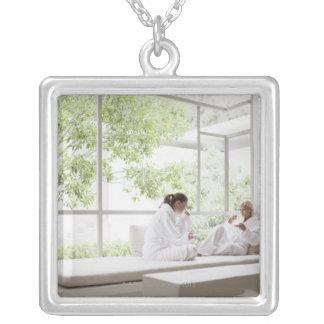 Women drinking tea in window silver plated necklace