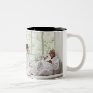 Women drinking tea in window Two-Tone coffee mug