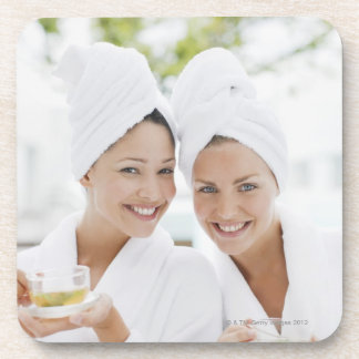 Women in bathrobes drinking tea at spa coaster