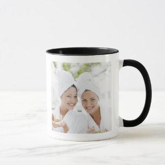 Women in bathrobes drinking tea at spa mug