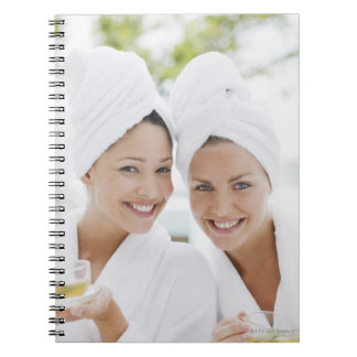 Women in bathrobes drinking tea at spa notebook