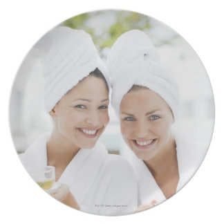 Women in bathrobes drinking tea at spa plate