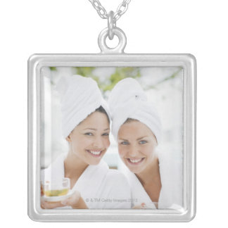 Women in bathrobes drinking tea at spa silver plated necklace