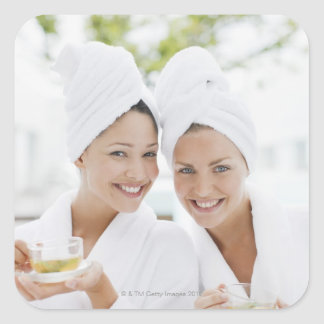 Women in bathrobes drinking tea at spa square sticker
