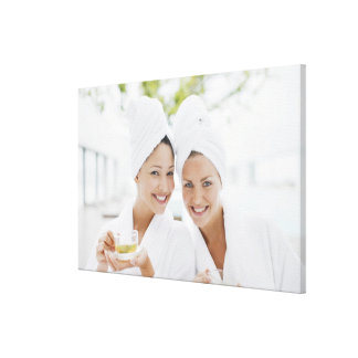Women in bathrobes drinking tea at spa stretched canvas print