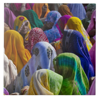 Women in colorful saris gather together large square tile