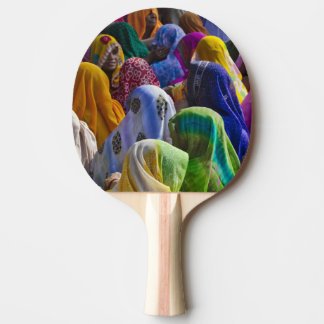 Women in colorful saris gather together ping pong paddle