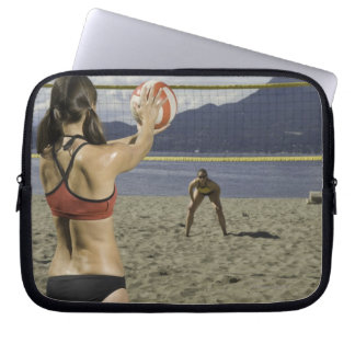 Women playing volleyball on beach laptop sleeve
