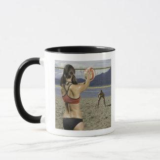 Women playing volleyball on beach mug