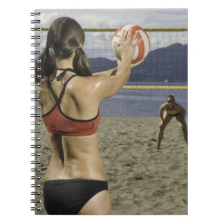 Women playing volleyball on beach notebook