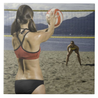 Women playing volleyball on beach tile