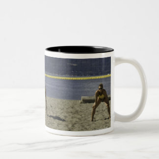 Women playing volleyball on beach Two-Tone coffee mug