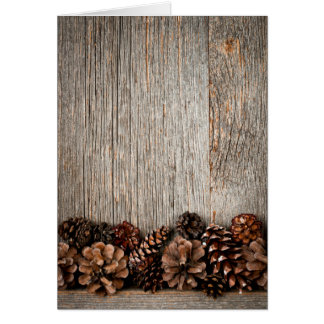 Wood background with pine cones note card