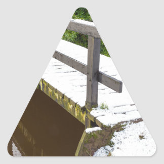 Wooden bridge covered with snow in winter triangle sticker