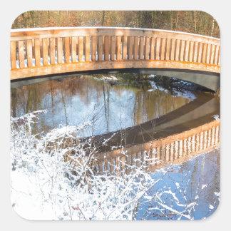 Wooden bridge snow and water in winter season square sticker