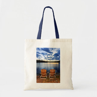 Wooden chairs at sunset on lake shore tote bag