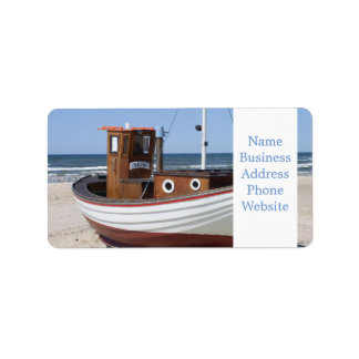 Wooden fishing boat on the beach. address label