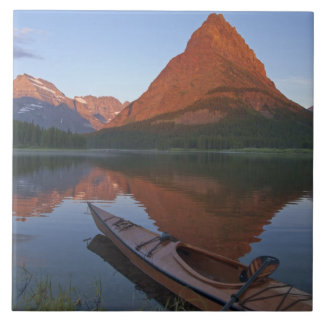 Wooden kayak in Swiftcurrent Lake at sunrise in Large Square Tile