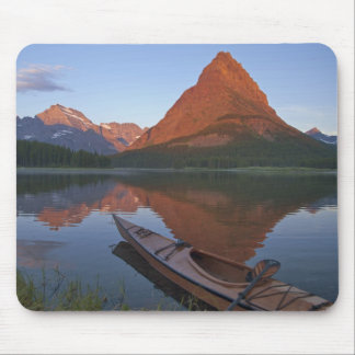 Wooden kayak in Swiftcurrent Lake at sunrise in Mouse Mat