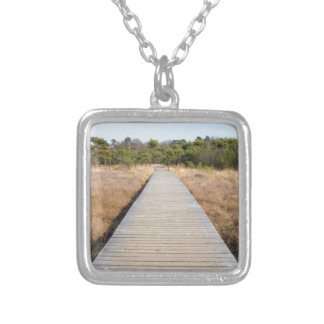 Wooden path in grass and forest winters landscape. square pendant necklace