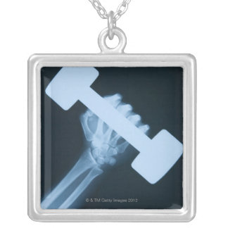 X-ray image of human hand with weight, close-up silver plated necklace