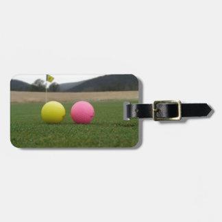 yellow and pink golf balls, luggage tag